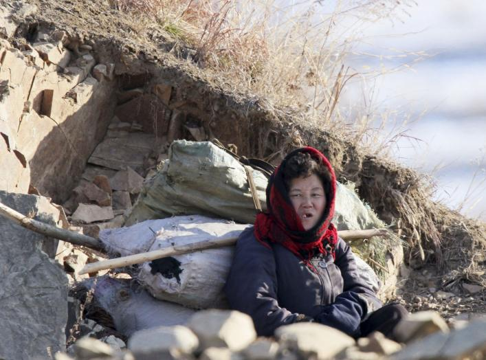 A North Korean woman rests on on the banks of Yalu River, in Sakchu county, North Korea, January 7, 2016. REUTERS/Jacky Chen
