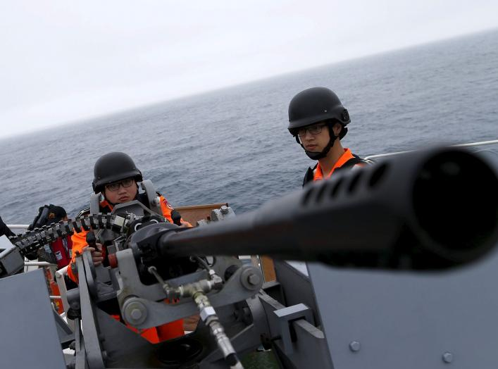 "Taiwanese Coast Guard Administration guard demonstrate a machine gun on the docks of the 3000-ton ""Ilan"" patrol ship at East China Sea, near Pengjia Islet, the northern most island controlled by Taiwan, April 9, 2016. REUTERS/Tyrone Siu"
