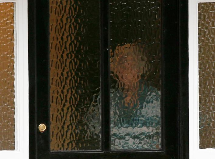 A person stands behind textured glass at an address which has been linked by local media to former British intelligence officer Christopher Steele, who has been named as the author of an intelligence dossier on President-elect Donald Trump.