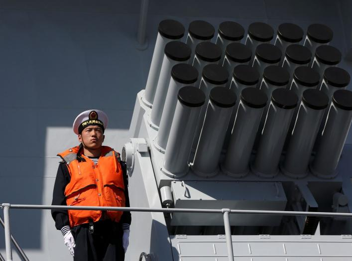 A Chinese serviceman stands beside a multibarrel rocket launcher on the deck of a naval vessel, upon its arrival to participate in Pakistan Navy's Multinational Exercise AMAN-17, in Karachi, Pakistan, February 9, 2017. REUTERS/Akhtar Soomro