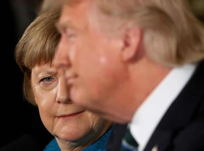 Germany's Chancellor Angela Merkel (L) gives U.S. President Donald Trump a look after he suggested they might have something in common, as he answered a question about his accusation that he had been wiretapped by former President Barack Obama, during the