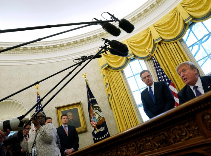 U.S. Trade Representative Robert Lighthizer stands behind U.S. President Donald Trump as Trump prepares to sign directives to impose tariffs on imported washing machines and solar panels in the Oval Office at the White House in Washington, U.S. January 23