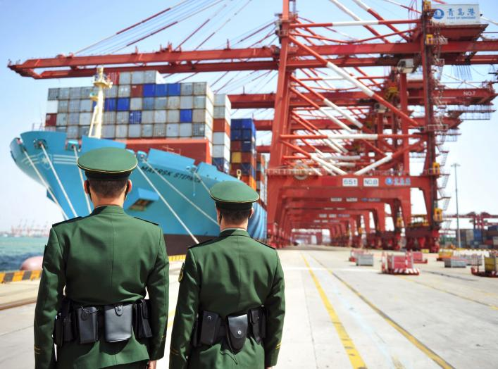 Police officers are seen in front of a cargo ship with containers at a port in Qingdao, Shandong province, China April 6, 2018. REUTERS/Stringer