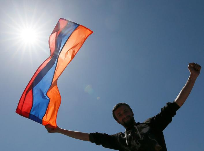 A man holds an Armenian state flag during a rally held by supporters of opposition leader Nikol Pashinyan in Yerevan, Armenia April 25, 2018. REUTERS/Gleb Garanich