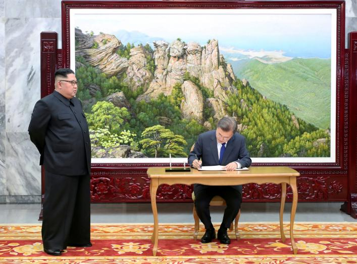 South Korean President Moon Jae-in signs a guestbook as North Korean leader Kim Jong Un looks on before their summit at the truce village of Panmunjom, North Korea, in this handout picture provided by the Presidential Blue House on May 26, 2018. Picture t