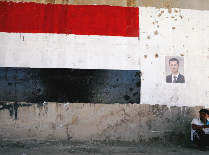 A man sits near a poster of Syrian President Bashar al Assad during the re-opening of the road between Homs and Hama in Talbisi, Syria June 6, 2018. REUTERS/Omar Sanadiki