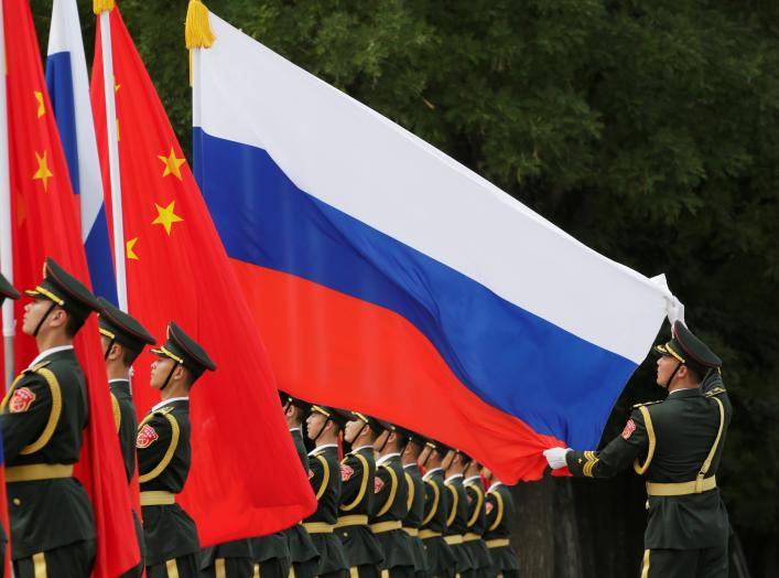 A military officer adjusts a Russian flag ahead of a welcome ceremony hosted by Chinese President Xi Jinping for Russian President Vladimir Putin outside the Great Hall of the People in Beijing, China June 8, 2018. REUTERS/Jason Lee