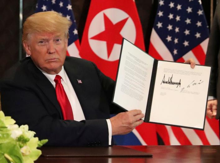 U.S. President Donald Trump shows the document, that he and North Korea's leader Kim Jong Un signed acknowledging the progress of the talks and pledge to keep momentum going, after their summit at the Capella Hotel on Sentosa island in Singapore June 12,