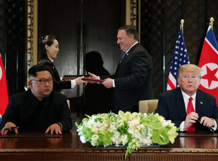 North Korea's leader Kim Jong Un looks at U.S. President Donald Trump as Kim's sister Kim Yo Jong exchanges document with U.S. Secretary of State Mike Pompeo at their summit at the Capella Hotel on Sentosa island in Singapore June 12, 2018. REUTERS/Jonath