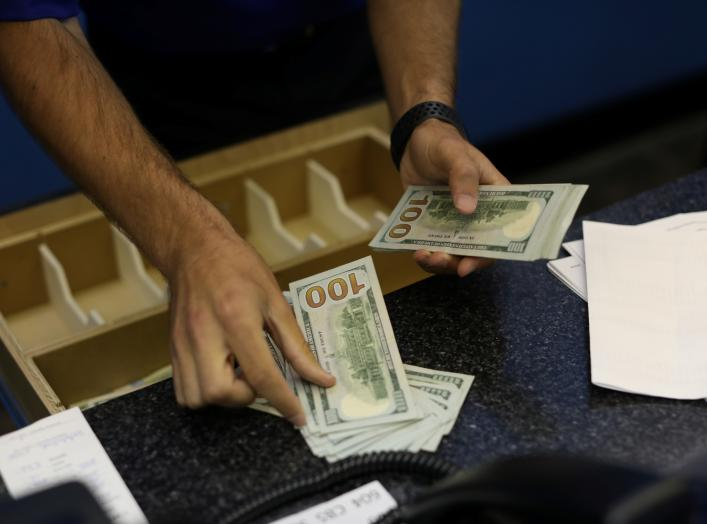 A teller is counting money before betting opens to the public at Monmouth Park Sports Book by William Hill, ahead of the opening of the first day of legal betting on sports in Oceanport, New Jersey, U.S., June 14, 2018. REUTERS/Mike Segar