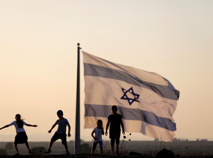 Israeli kids play next to an Israeli flag next to the Israeli Syrian border at the Israeli-occupied Golan Heights, Israel July 23, 2018. REUTERS/Ronen Zvulun
