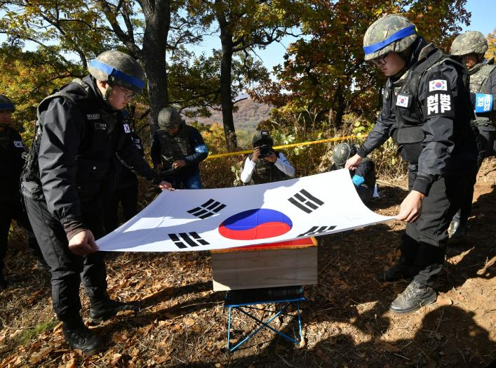 Members of South Korea's Defence Ministry recovery team cover a casket containing a piece of bone believed to be the remains of an unidentified South Korean soldier killed in the Korean War with the national flag in the Demilitarized Zone (DMZ) dividing t