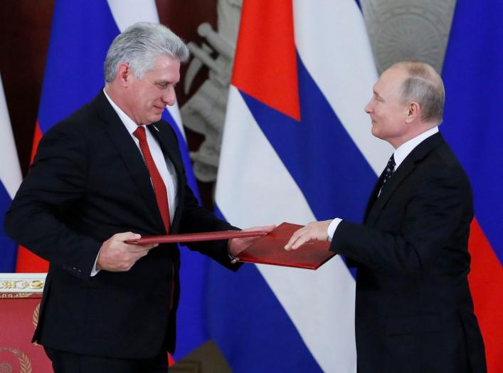 Russian President Vladimir Putin and Cuban President Miguel Diaz-Canel exchange documents following their meeting at the Kremlin in Moscow, Russia November 2, 2018. REUTERS/Maxim Shemetov
