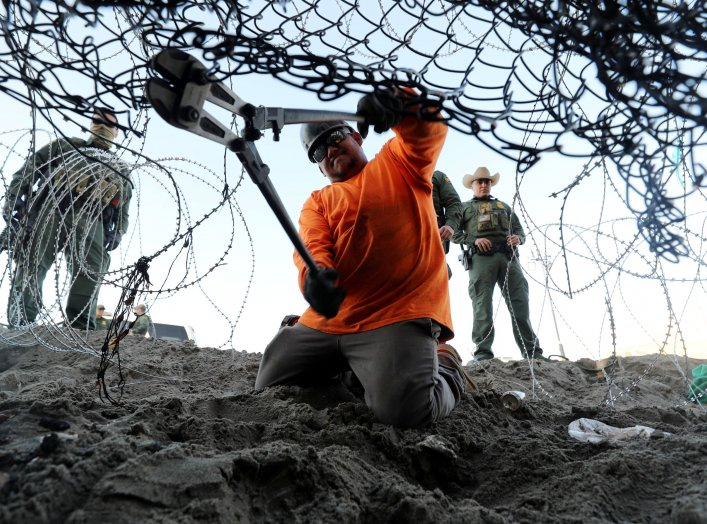 A worker on the U.S. side installs concertina wire along the border wall with the United States as seen from Tijuana, Mexico, December 11, 2018. REUTERS/Mohammed Salem