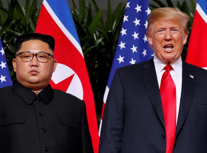 FILE PHOTO: U.S. President Donald Trump and North Korean leader Kim Jong Un react at the Capella Hotel on Sentosa island in Singapore June 12, 2018. REUTERS/Jonathan Ernst/File Photo