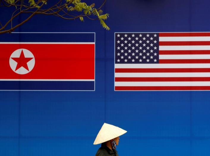 A person walks past a banner showing North Korean and U.S. flags ahead of the North Korea-U.S. summit in Hanoi, Vietnam, February 25, 2019. REUTERS/Kim Kyung-Hoon TPX IMAGES OF THE DAY