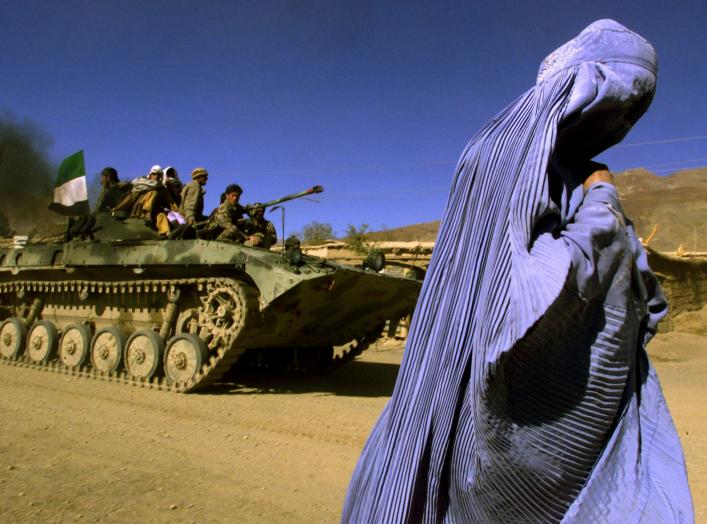 FILE PHOTO: An Afghan woman wearing a traditional Burqa walks on the side of a road as a Northern Alliance APC, (Armoured Personnel Carrier) carrying fighters and the Afghan flag, drives to a new position in the outskirts of Jabal us Seraj, some 60kms nor