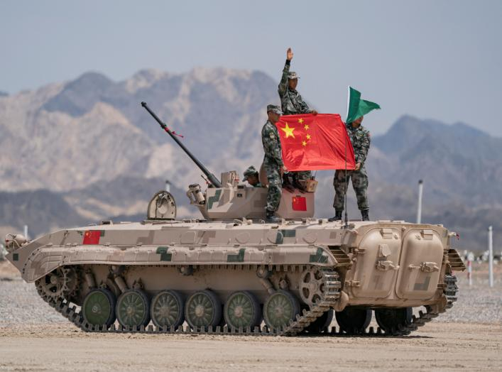 Chinese soldiers of People's Liberation Army (PLA) pose for photos with a Chinese national flag on a tank during the Suvorov Attack contest of the International Army Games 2019 in Korla, Xinjiang Uighur Autonomous Region, China August 4, 2019. Reuters
