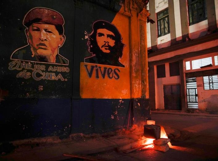 "Images depicting Venezuela's late president Hugo Chavez (L), with words that read ""The best friend of Cuba"", and late revolutionary hero Ernesto ""Che"" Guevara are seen over a pot of caldosa, a typical Cuban stew during celebrations of the 59th anniversary"