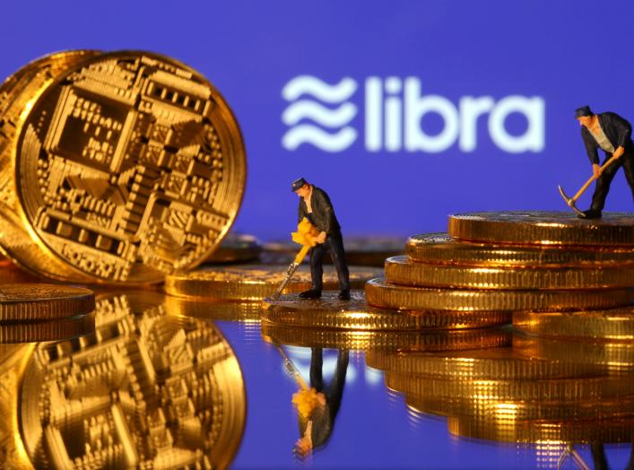 Small toy figures are seen on representations of virtual currency in front of the Libra logo in this illustration picture, June 21, 2019. REUTERS/Dado Ruvic