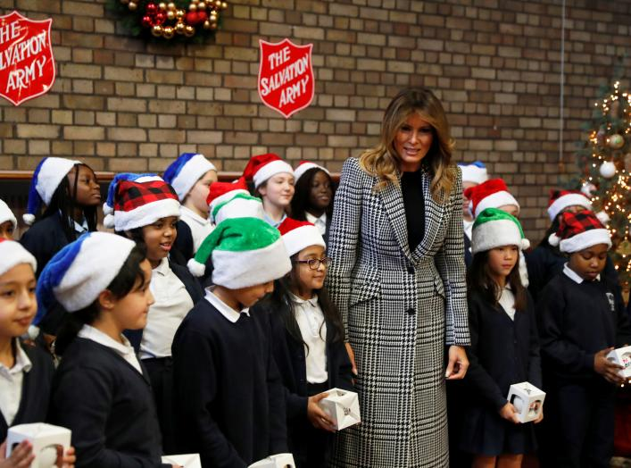 U.S. first lady Melania Trump poses with a children choir after joining local school students and U.S. Marines stationed at the U.S. Embassy, wrapping holiday presents to be donated to the Salvation Army, at the Salvation Army Clapton Center
