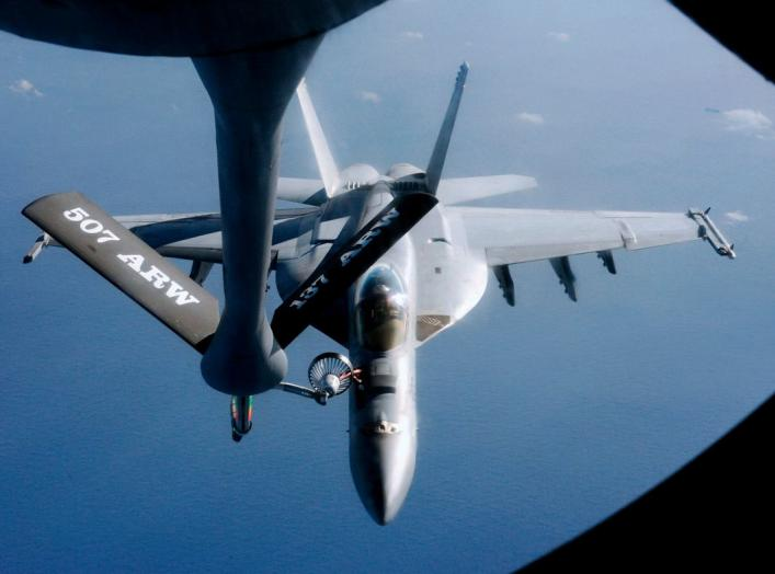 An FA-18 air fighter from the U.S. carrier George Washington is being refuelled by an air tanker over the Pacific near Okinawa Island, southern Japan, December 9, 2010. REUTERS/Kyodo (JAPAN - Tags: MILITARY TRANSPORT) JAPAN OUT. NO COMMERCIAL OR EDITORIAL