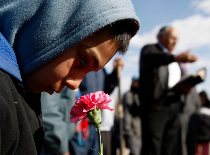 A boy holds a flower during the funeral of 16-year-old Karina Ivette Delgado in Ciudad Juarez February 3, 2011. Delgado was killed in a crossfire between suspected car thieves and federal agents on Sunday, according to local media.  REUTERS/Gael Gonzalez