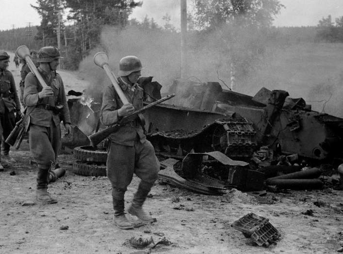 Finnish soldiers carrying Panzerfäuste on their shoulders pass by the remains of a destroyed Soviet T-34 tank at the Battle of Tali-Ihantala