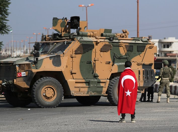 Boy wearing a Turkish flag stands in front of a Turkish military vehicle in the town of Tal Abyad