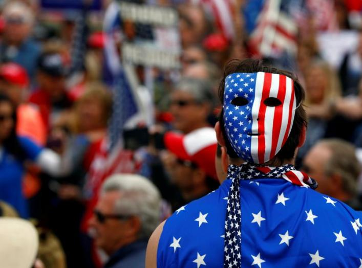 A pro-Trump rally participant wears a U.S. flag during the Southern California Make America Great Again march in support of President Trump, the military and first responders at Bolsa Chica State Beach in Huntington Beach, California, U.S. March 25, 2017.