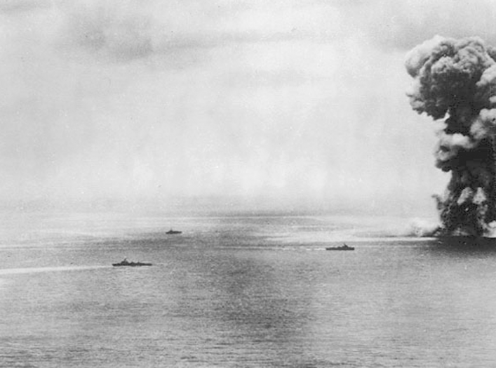 Japanese battleship Yamato moments after exploding, after receiving massive bomb and torpedo damage from US Navy carrier planes, north of Okinawa on 7 April 1945 during Japanese Operation Ten-Go. Three Japanese destroyers are nearby.
