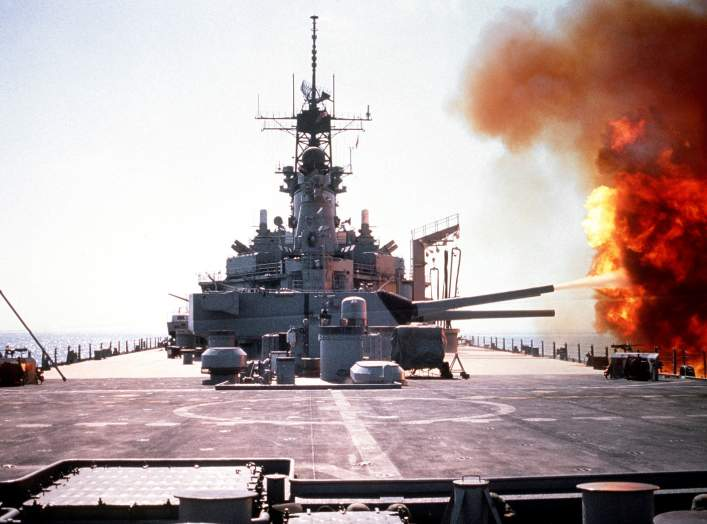 The battleship USS WISCONSIN (BB-64) fires a round from one of the Mark 7 16-inch/50-caliber guns in its No. 3 turret during Operation Desert Storm. The ship's target is an Iraqi artillery battery in southern Kuwaiti.
