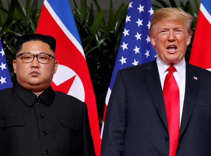 FILE PHOTO: U.S. President Donald Trump and North Korean leader Kim Jong Un react at the Capella Hotel on Sentosa island in Singapore June 12, 2018. REUTERS/Jonathan Ernst/File Photo