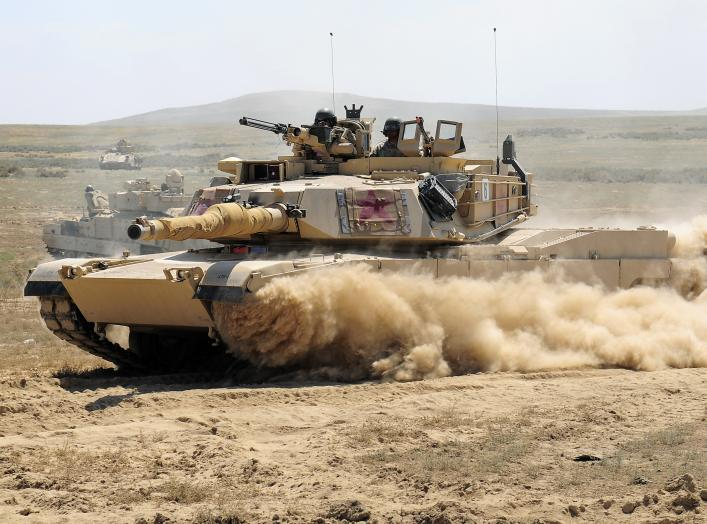A U.S. Army M1A2 Abrams main battle tank assigned to the Minnesota National Guard races through a breach in a barbed wire obstacle during the 116th eXportable Combat Training Exercise at the Orchard Combat Training Center, Idaho, Aug. 21, 2014