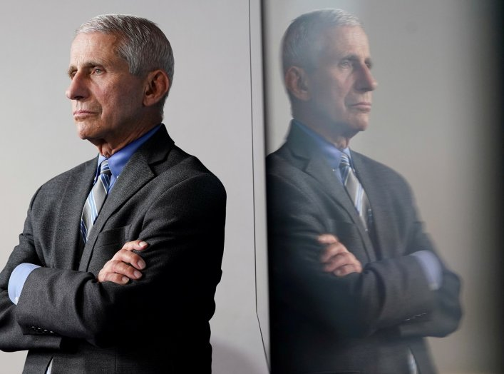 National Institute of Allergy and Infectious Diseases Director Dr. Anthony Fauci is reflected in a video monitor behind him on stage as he listens to the daily coronavirus task force briefing at the White House in Washington, U.S., April 8, 2020. REUTERS/