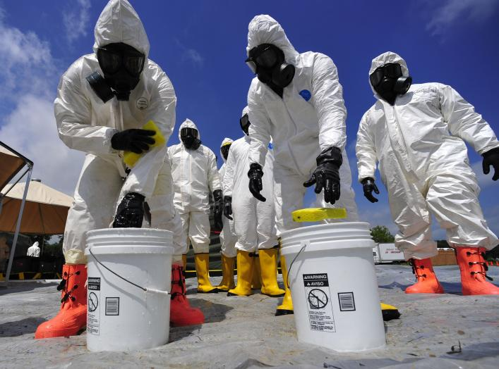 U.S. Soldiers from the 457th Chemical Battalion sponge off their level A protective suits after a simulated nuclear detonation scenario at the Muscatatuck Urban Training Center in Indiana July 19, 2010, during exercise Vibrant Response 10.2.