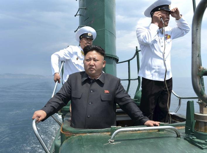 North Korean leader Kim Jong Un stands on the conning tower of a submarine during his inspection of the Korean People's Army Naval Unit 167 in this undated photo released June 16, 2014.