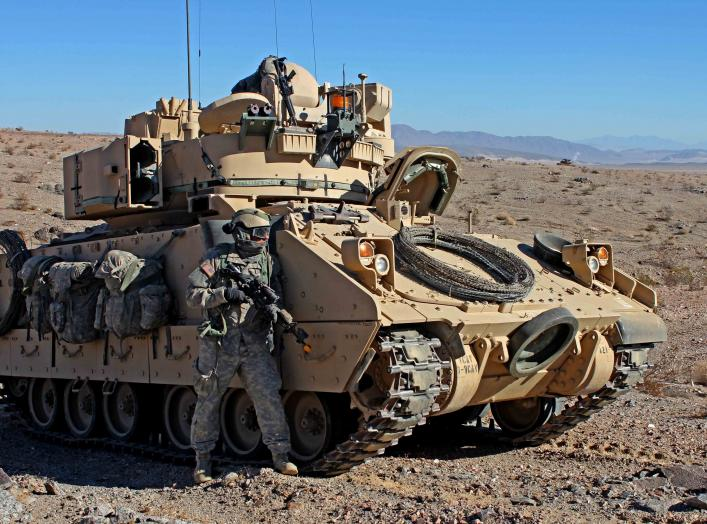 U.S. Army Soldier from the 3rd Armored Brigade Combat Team, 1st Infantry Division pulls security next to a M2 Bradley Infantry Fighting Vehicle during Decisive Action rotation 13-03 on Jan. 19, 2013 at the National Training Center in Fort Irwin, Calif. De