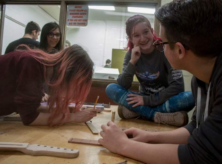 Students work together when they build guitars in class, reinforcing what they learn.  James Cordero, CC BY-SA
