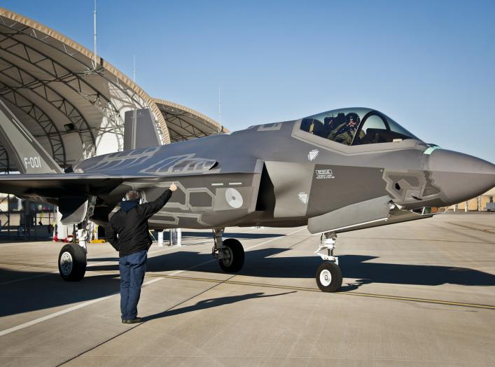 Maj. Laurens Vijge, a Royal Netherlands Air Force pilot, salutes his Lockheed Martin crew chief as he taxis out for the first flight in the F-35A Lightning II. Vijge became the first RNLAF pilot to fly the joint strike fighter.