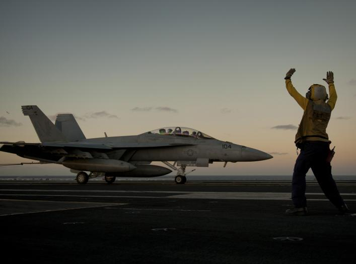 U.S. Navy Aviation Boatswain's Mate 3rd Class Tilford Breedlove signals to the pilot of an F/A-18F Super Hornet aircraft, with the Strike Fighter Squadron 22, during an arrested landing on the flight deck of aircraft carrier USS Carl Vinson (CVN-70) in th