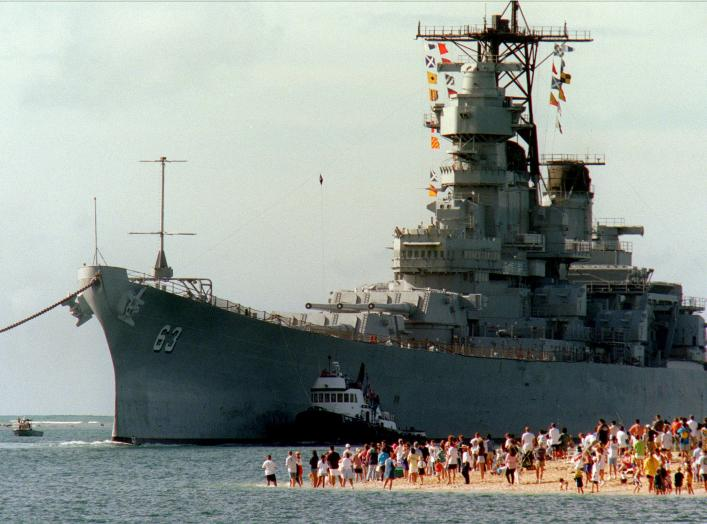 People gather on the beach to see the battleship USS Missouri (BB 63) enter the channel into Pearl Harbor, Hawaii, on June 22, 1998.
