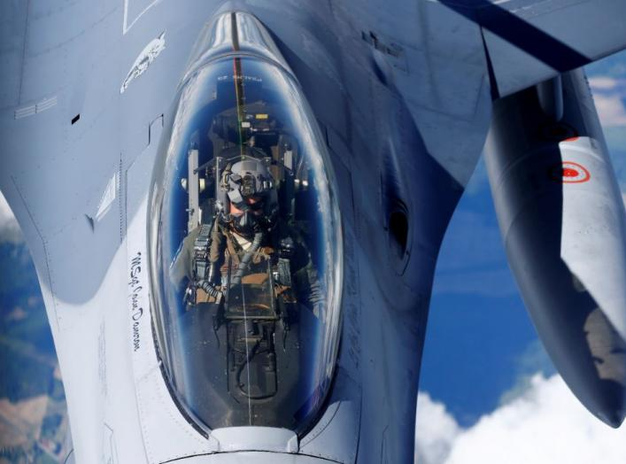 A U.S. Air Force pilot looks at a KC-135 aerial refueling aircraft as he refuels his F-16 fighter during the U.S.-led Saber Strike exercise in the air over Estonia June 6, 2018. REUTERS/Ints Kalnins