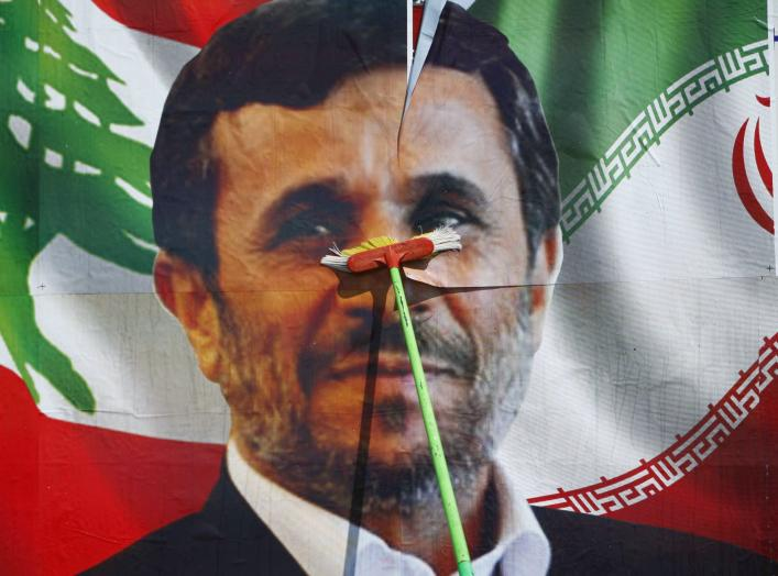 A worker puts up a billboard poster of Iranian President Mahmoud Ahmadinejad in Deir al-Zahrani village at southern Lebanon October 9, 2010. Ahmadinejad plans to visit Lebanon next Wednesday and he is expected to tour villages in southern Lebanon. REUTERS