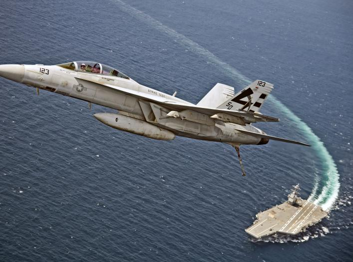 An F/A-18F Super Hornet assigned to Air Test and Evaluation Squadron (VX) 23 flies over the aircraft carrier USS Gerald R. Ford (CVN 78). The aircraft carrier is underway conducting test and evaluation operations.