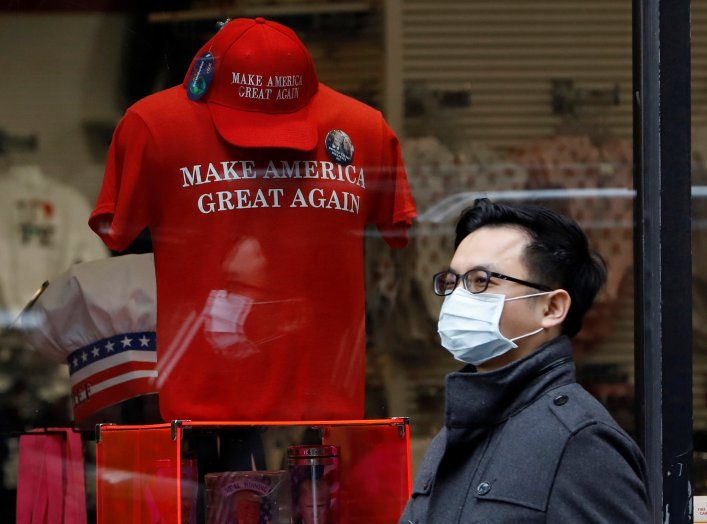 "A man in a surgical mask walks by goods for sale emblazoned with U.S. President Donald Trump's 2016 campaign slogan ""Make America Great Again"", after more cases of coronavirus were confirmed in New York City, New York, U.S., March 10, 2020. REUTERS/Andrew"