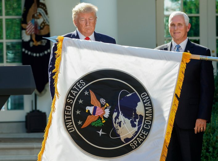 U.S. President Donald Trump stands behind a U.S. Space Command flag with Vice President Mike Pence at an event to officially launch the United States Space Command in the Rose Garden of the White House in Washington, U.S., August 29, 2019. REUTERS/Kevin L