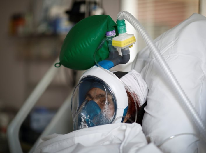 A patient suffering from coronavirus disease (COVID-19) wears a full-face Easybreath snorkelling mask given by sport chain Decathlon and turned into a ventilator for coronavirus treatment at the intensive care unit at Ambroise Pare clinic in Neuilly-sur-S