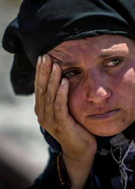 A woman reacts as she rests from walking back to Tel Abyad town, Raqqa governorate, after fleeing Maskana town in the Aleppo countryside June 16, 2015. With a string of victories over Islamic State, Syria's Kurds are proving themselves an ever more depend