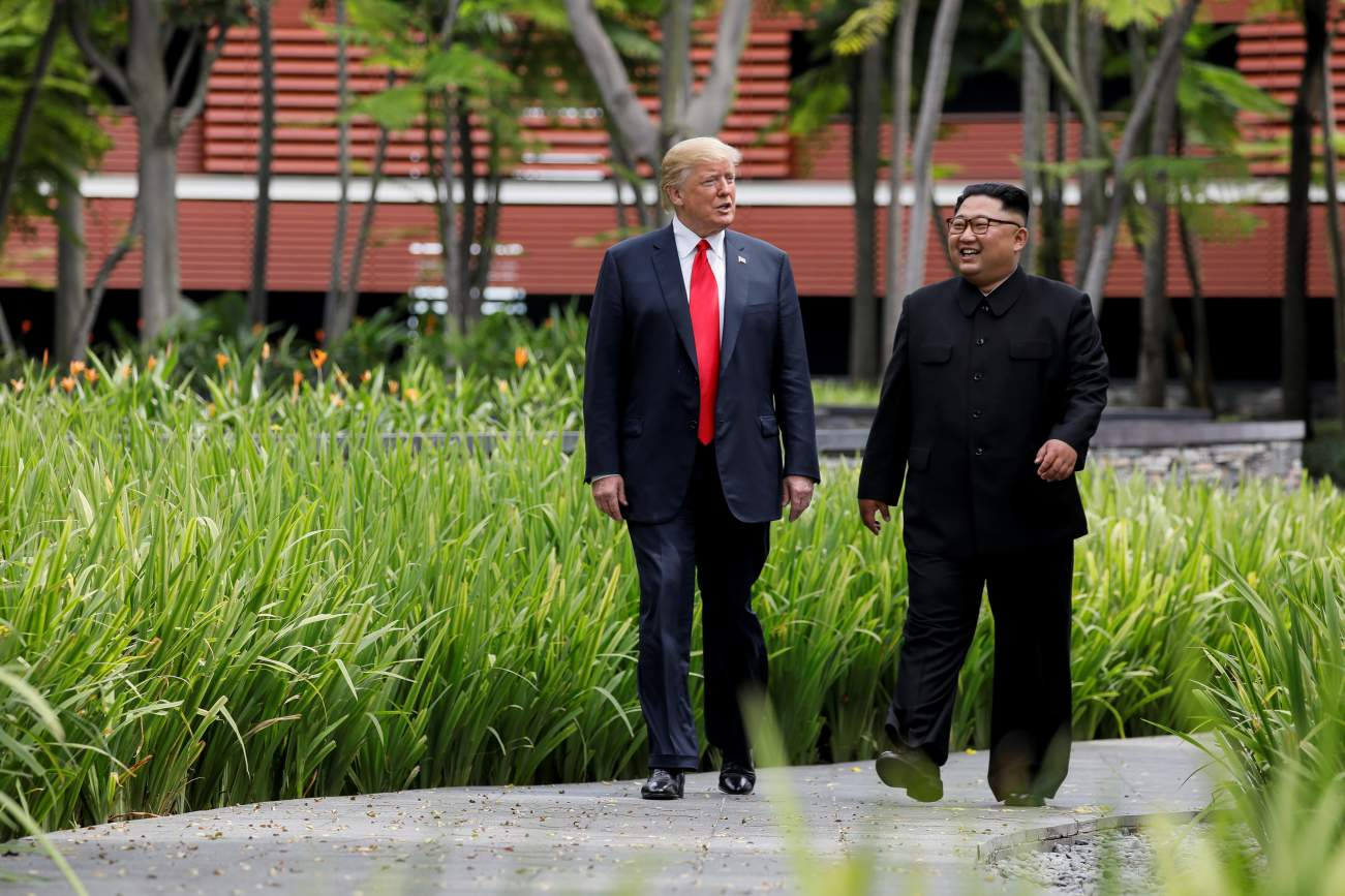 U.S. President Donald Trump and North Korea's leader Kim Jong Un walk together before their working lunch during their summit at the Capella Hotel on the resort island of Sentosa, Singapore June 12, 2018. Picture taken June 12, 2018. REUTERS/Jonathan Erns